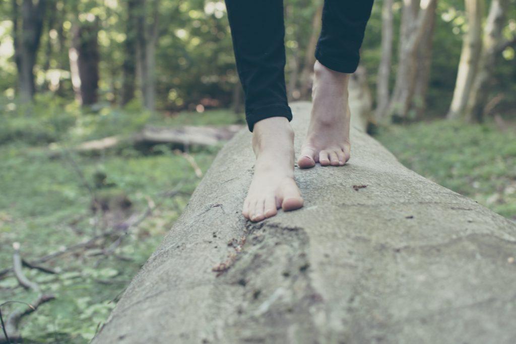 Das Bild zeigt nackte Fäße balancierend auf einem Baumstamm im Wald.