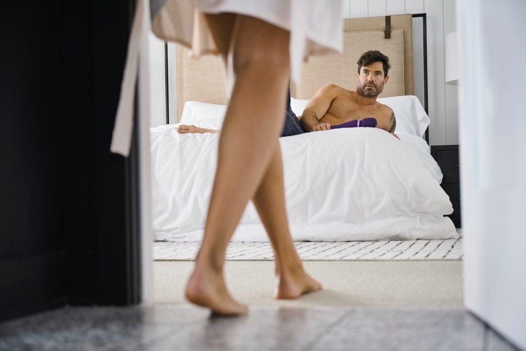 Das Bild zeigt eine Frau ins Schlafzimmer gehen, in dem der Mann bereits auf dem Bett liegt und auf sie wartet.