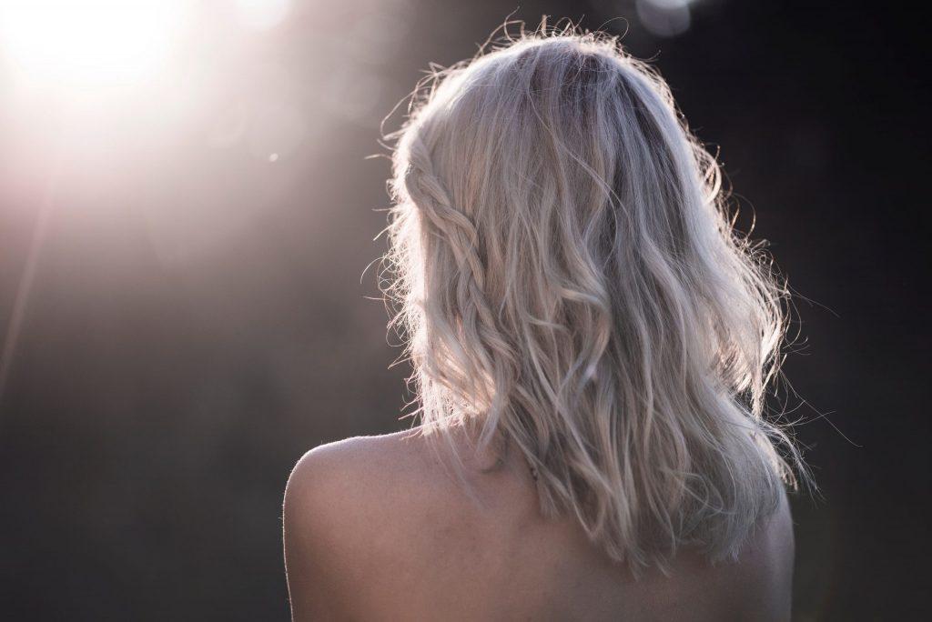 Das Bild zeigt eine blonde Frau mit nacktem Rücken von hinten.