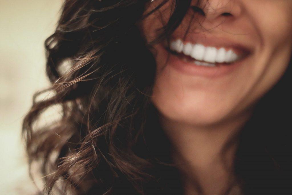 Das Bild zeigt eine junge, lächelnde Frau mit dunklen Locken.