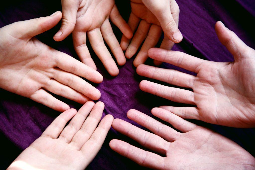Das Bild zeigt Hände im Kreis auf einem lila Untergrund.