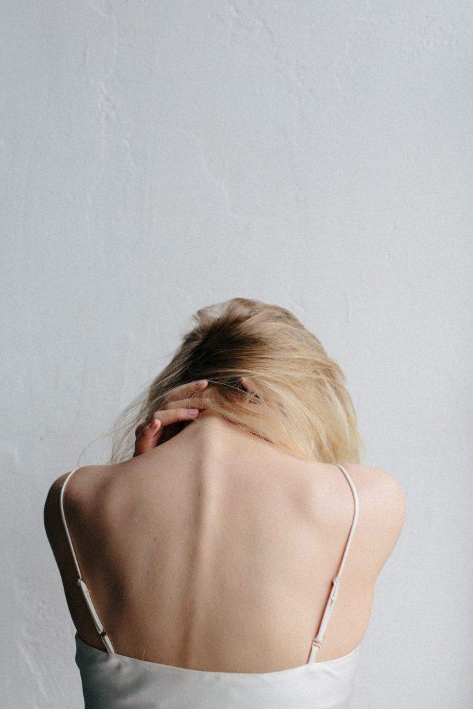 Das Bild zeigt eine junge Frau von hinten in weißem tief geschnittenen Top, wie sie den Kopf nach vorne legt.