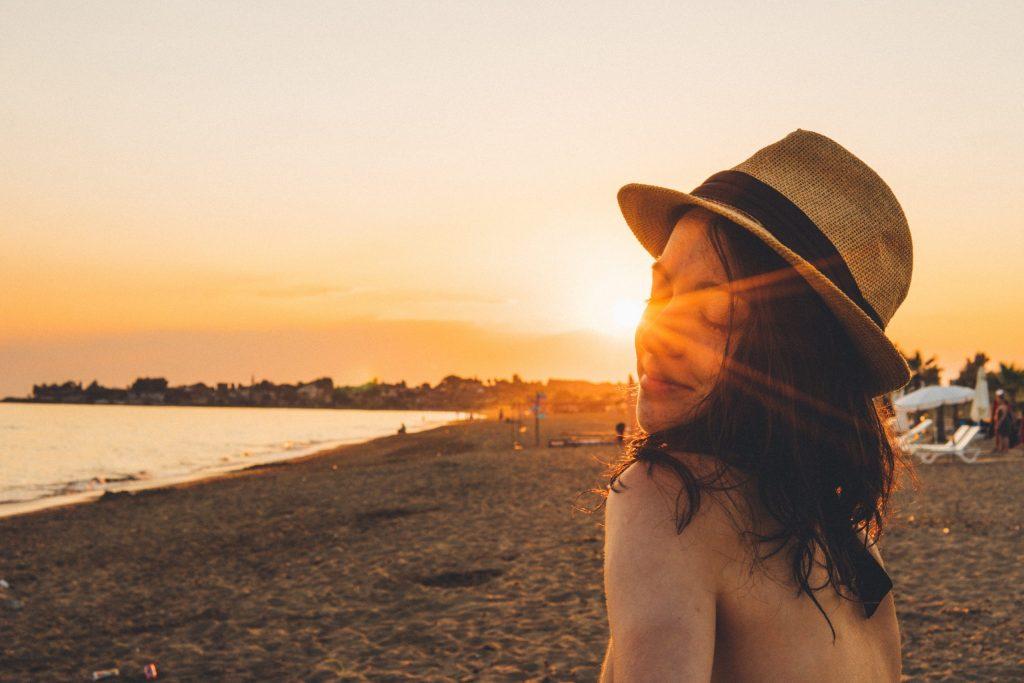 Das Bild zeigt eine junge Frau mit Sonnenhut am Strand in der Abendsonne stehen.