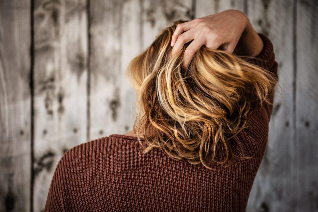 Das Bild zeigt eine junge Frau mit blonden, schulterlangen Haaren von hinten, wie sie sich in die Haare greift.