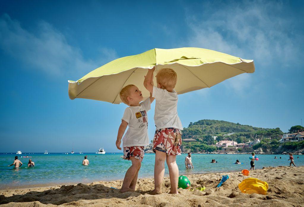 Das Bild zeigt Kinder am Strand unter einem Sonnenschirm.
