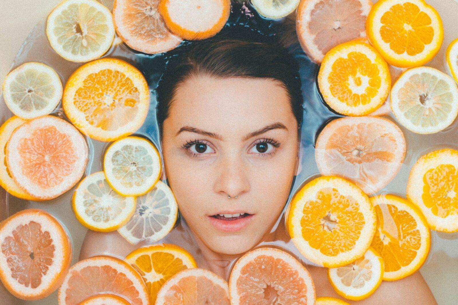 Das Bild zeigt eine Frau mit Zitrusfrüchten um ihr Gesicht.